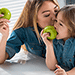 mother and daughter both eating healthy green apples